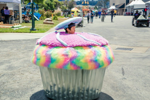 A young boy wearing a decorated hat drives a vehicle built to look like a giant cupcake.