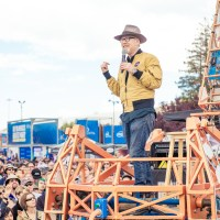 Adam Savage giving a speech while standing on the Electric Giraffe in front of a large crowd.