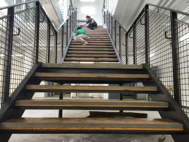 Surface Project installing our stair treads, made by apprentice craftspeople. Photo by Will Holman