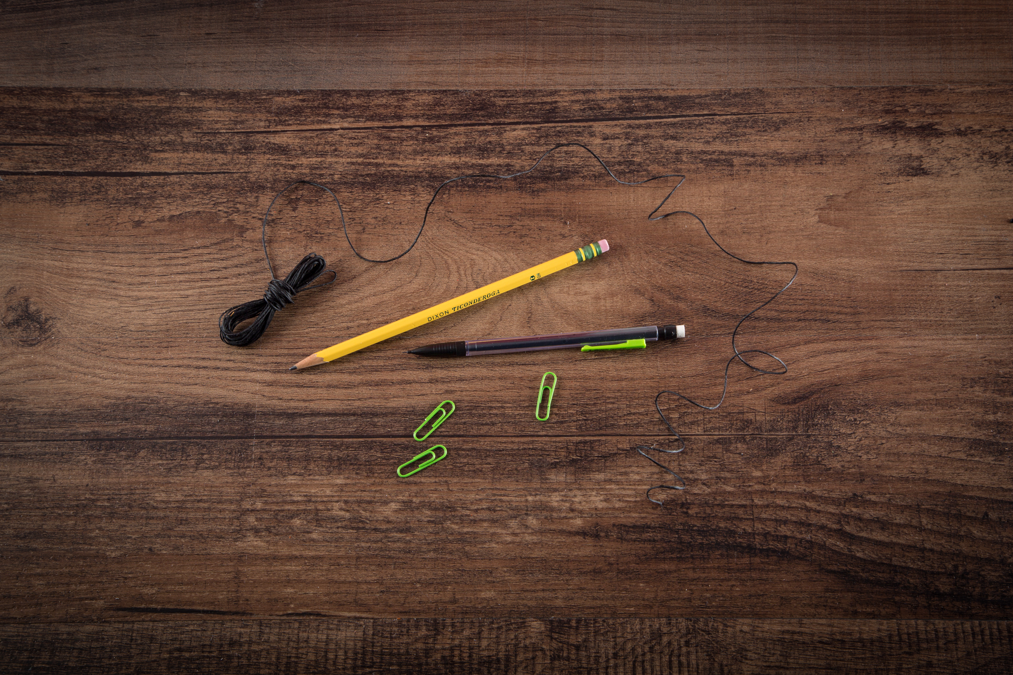 String, pencils, and paperclips on a wooden table.