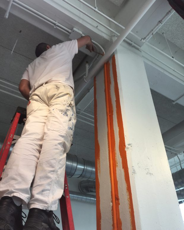 Sign painter extraordinaire Greg Gannon (@6reg6annon on Instagram) painting the columns with emergency shut-offs bright orange in the shops. Photo by Will Holman