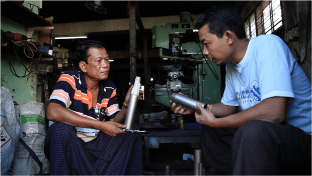 A Proximity Designs engineer speaks to machinist about a prototype of the Lotus solar irrigation pump.