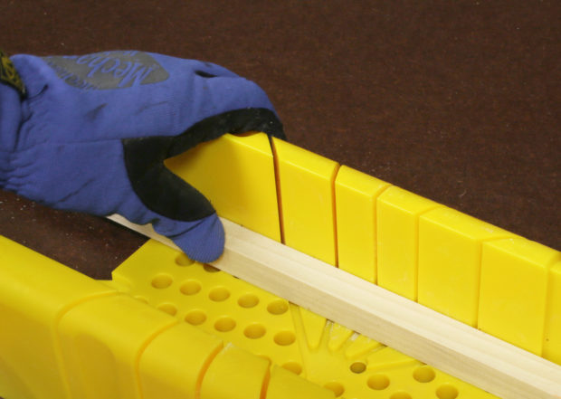 Figure 5. Hold the wood firmly against the opposite fence of the miter box.