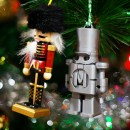 Two christmas ornaments side by side, one traditional nutcracker red and black, one 3D printed grey Makey nutcracker in a christmas tree.