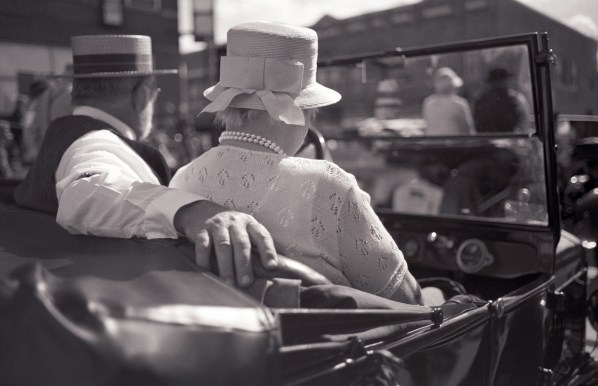 Rear view of man in straw hat and woman in hat with bow sitting and driving in Model T car.