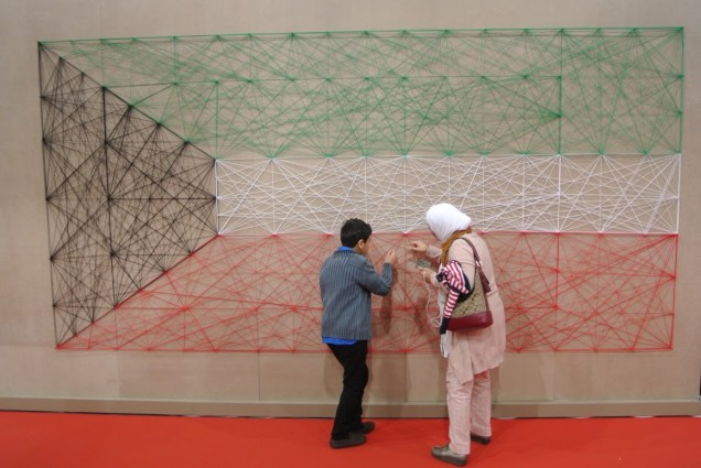 Inspecting the Kuwaiti national flag, made from string stretched across a large part of the wall.