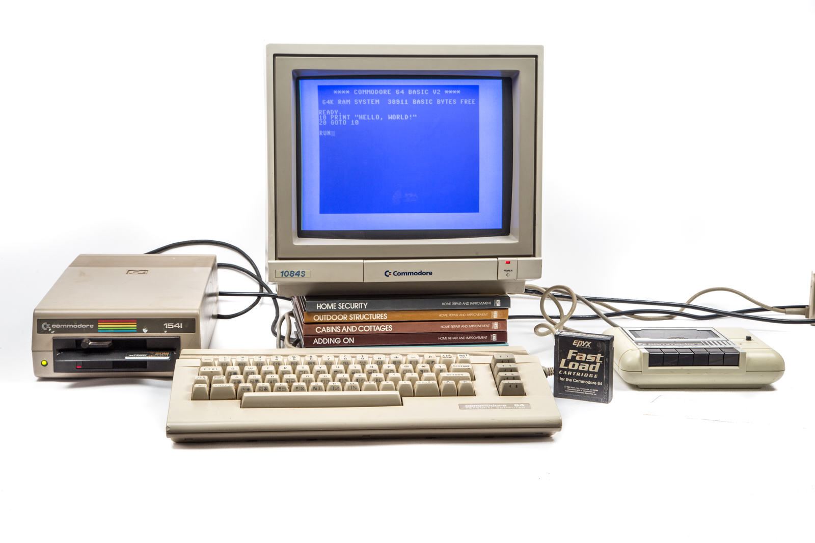 """A beige Commodore 64 computer terminal on a white backdrop. The program for """"Hello World"""" is on the screen."""