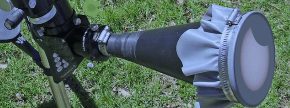 A DIY pinhole projector attached to a telescope in a grassy field.