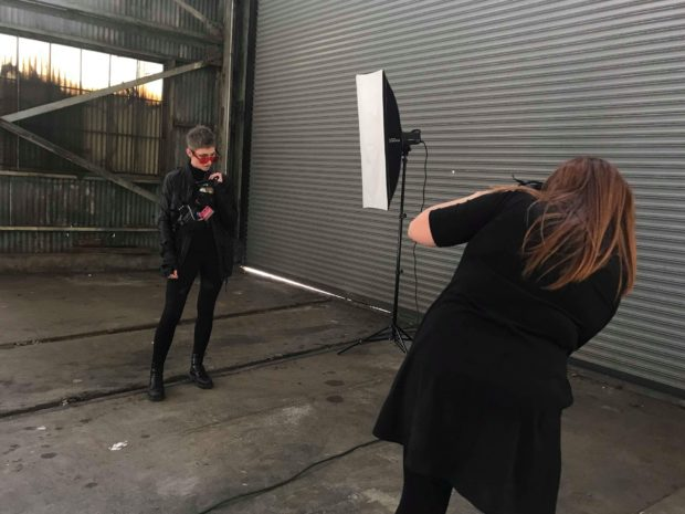 A woman stands in front of strobe photography lights while another woman with her back to the camera takes a photo.