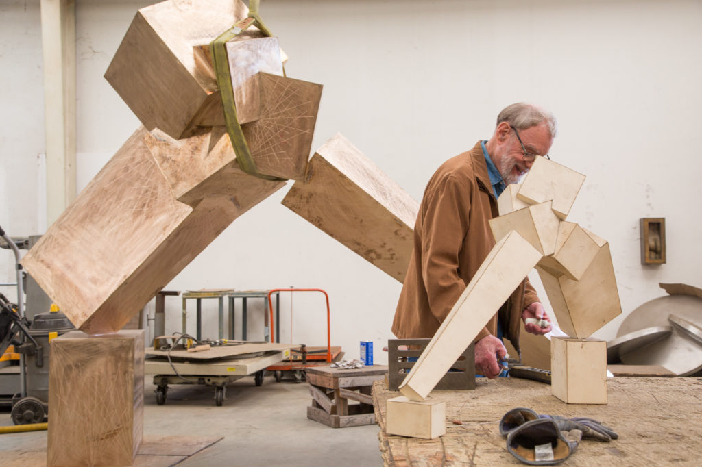Bruce Beasley observed a papercraft sculpture on a table next to a large-scale bronze version.