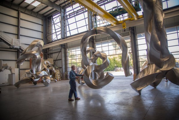 Bruce Beasley moves a twisted metal sculpture dangling from an overhead crane across a large warehouse of other sculptures.