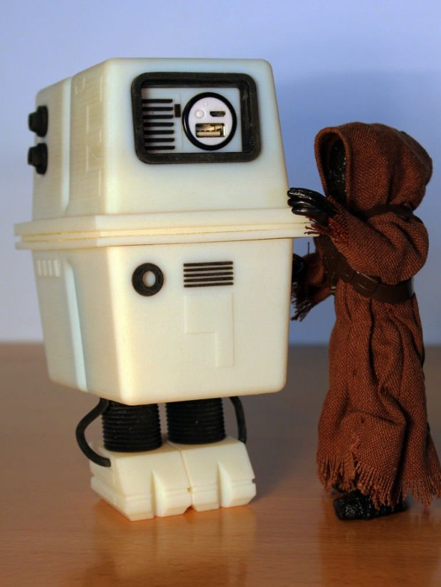 A white boxy robot stands next to a brown jawa action figure in a brown robe.