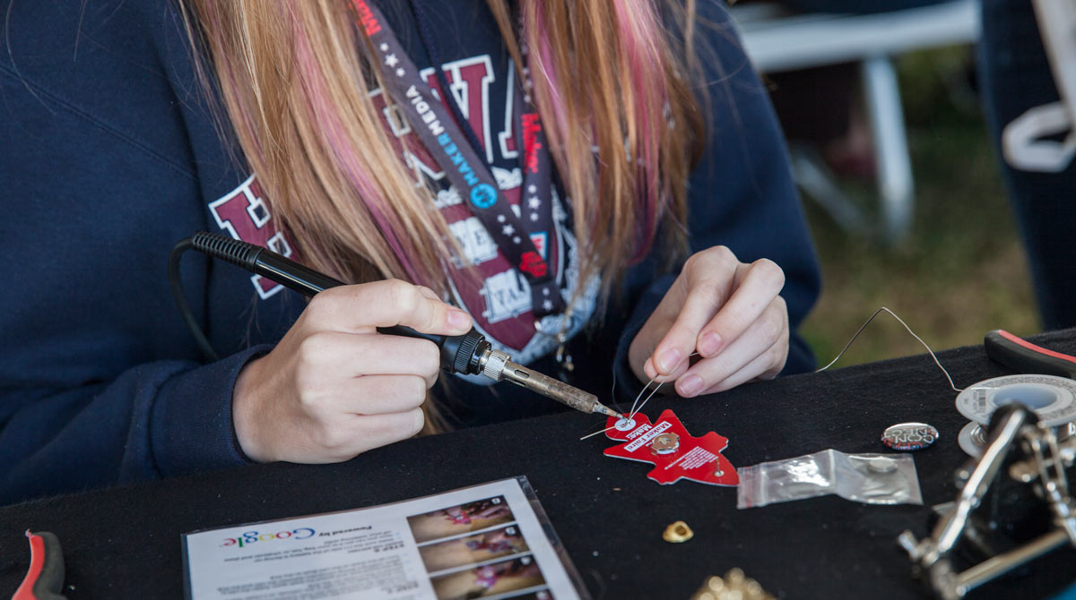 a young woman sitting at a table soldering the legs of an LED on the back of a small rocket shaped wearable pin