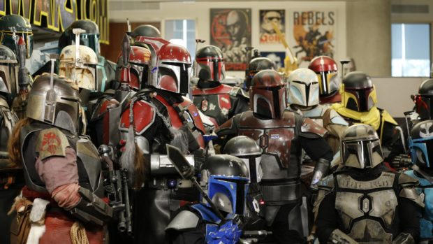 A group of people dressed in multicolored Mandalorian armor from Star Wars stand assembled.
