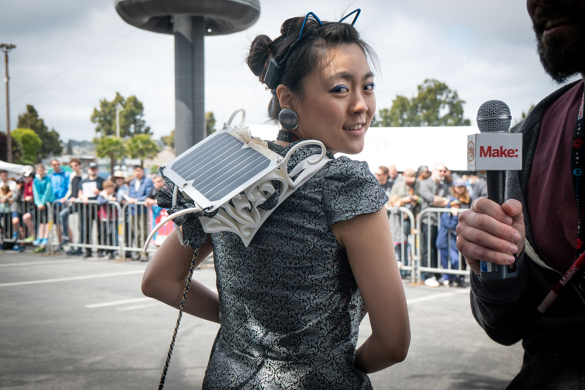Kitty Yeung stands with her back to the camera looking over one shoulder, displaying her 3D printed solar panel wearable recharging station on her back.