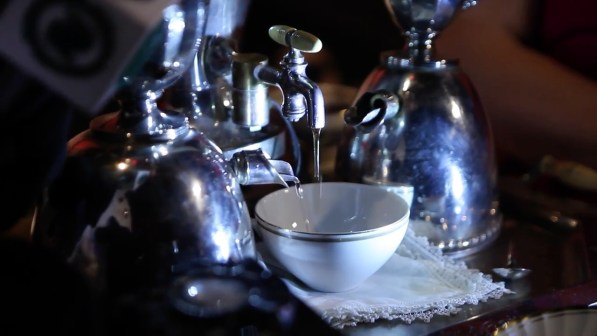 A sterling silver tea service robot pours tea mixed with liquer into a fine china cup.