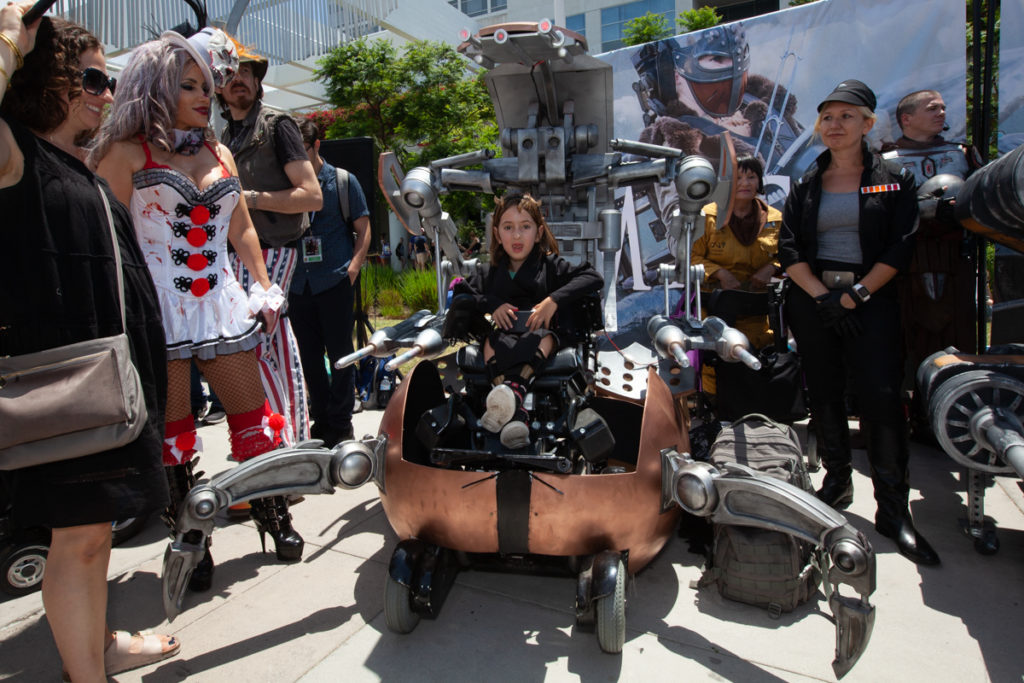 People admire a young girl sitting on her wheelchair disguised as a large futuristic mechanical robot.