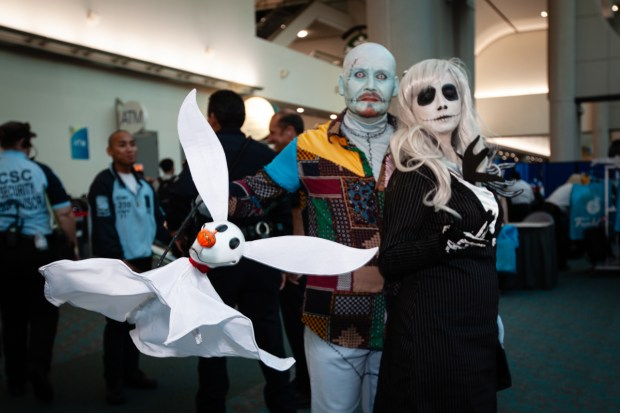 A couple is dressed as gender-swapped Jack Skellington and Sally with a Zero puppet.