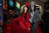 A couple stand dressed in red and gray victorian finery