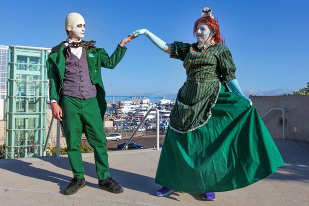 A couple holds hands dressed in Nightmare before Christmas crossed with Batman and the Joker cosplay