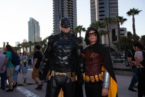 Batman and Robin stand outside.