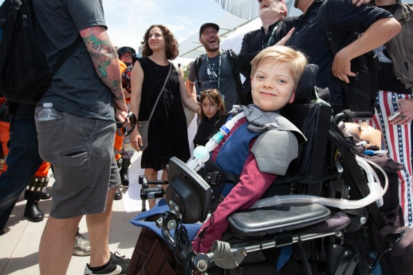 A young boy smiles into the camera while sitting on an undecorated wheelchair.