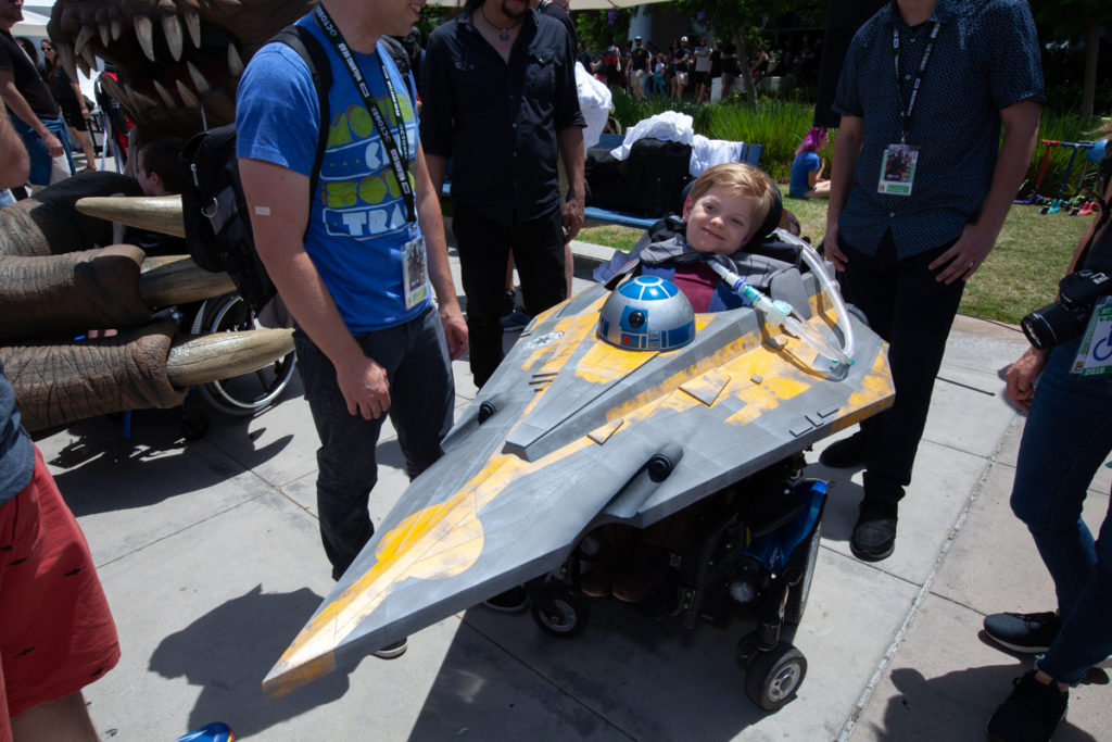 A young boy sits in a wheelchair disguised as a Jedi Starfighter space craft.