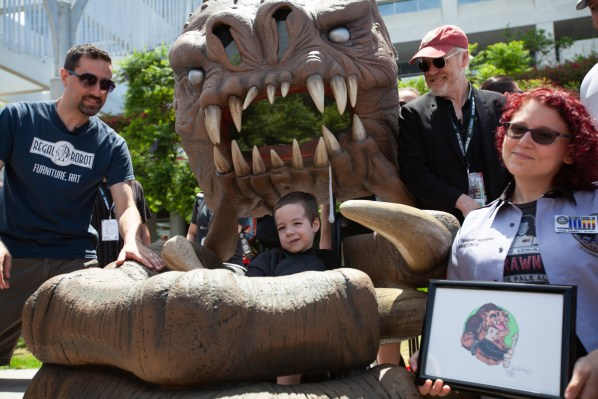 A small boy sits in a wheelchair disguised as a large brown alien creature clutching him with its paw.