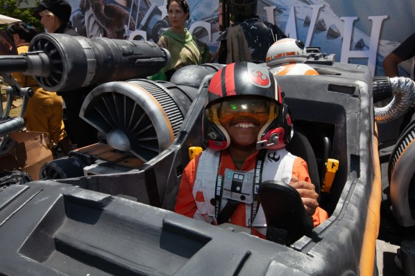 A boy dressed as an x-wing pilot smiles into the camera from within his space craft wheelchair
