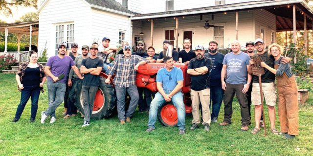 Group of 20 mostly men sit on and surround a red tractor