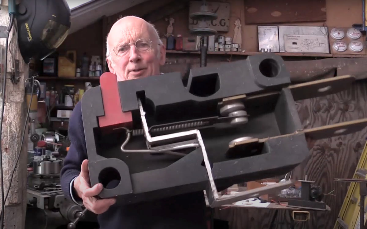 Tim Hunkin holds an oversized cross section of a two-pronged electrical plug