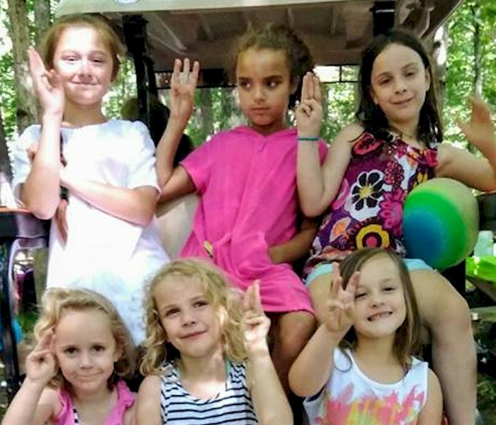 Daisy Girl Scouts showing the promise sign.