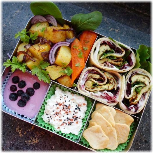 Lunchbots Bento Cinco gefüllt mit Omelette-Radicchio-Spinat-Tortillawraps, Pfannengemüse, Hüttenkäse, Crackern und Blaubeerjoghurt