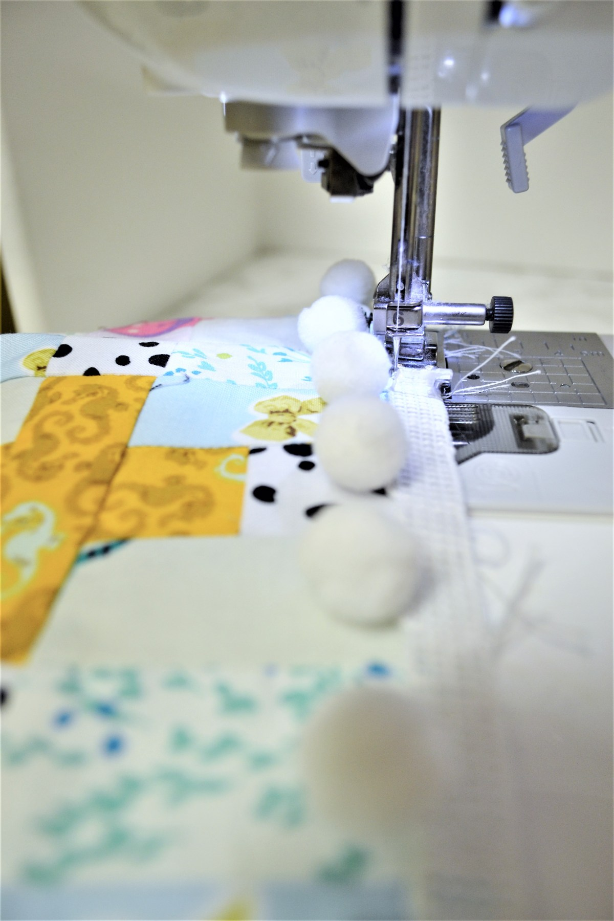 How to Add Pompom Trim to a Quilt - sew pompoms to quilt top