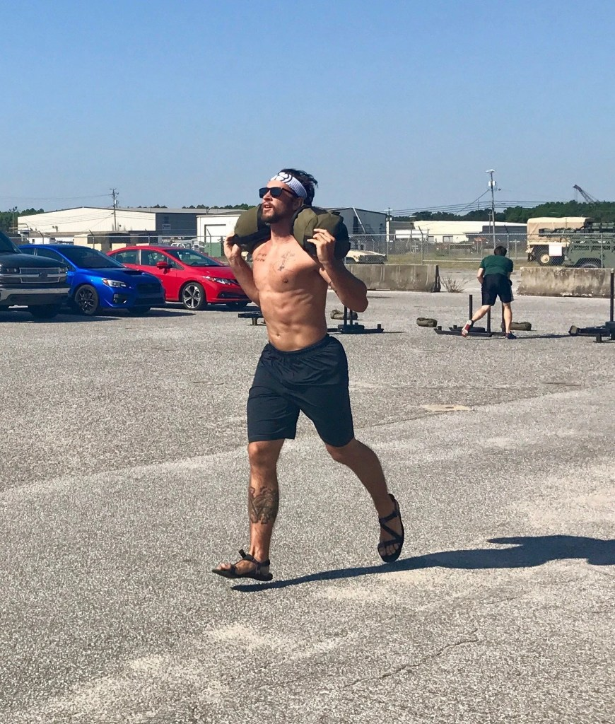 athlete running with sand bag