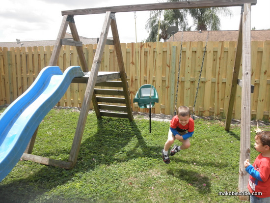 Kids playing on backyard swingset
