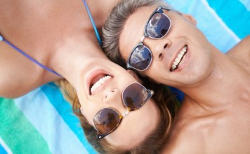 Happy couple in sunglasses lying on the beach