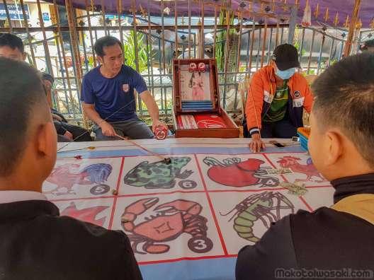 小さな市場では賭博中。ミャンマー式に似ている。