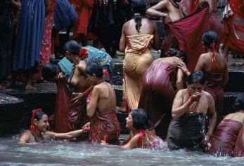 Steve McCurry,Nepaliese women bathing in Bagmati River, Kathmandu, Nepal, 1984Rejoicing in the renewal of life that the monsoon brings, women gather at the Baghmati River in Kathmandu for a ceremonial bath. They honor Parvati wife of the Hindu God Siva, who dwells among the peaks and sends the streams cascading to the plains.National Geographic: Priit J. Vesilind. Monsoons: Life Breat of Half of the World (December 1984, vol 166(6)), 712-747Women give thanks for the renewing rains through ritual washing in the Baghmati River. Teej festival, Kathmandu, Nepal.