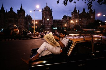 Steve McCurry, India, 50 Years After, 06/96, 1996. Man Reading a Newspaper on a Taxi. INDIA-10309NF2