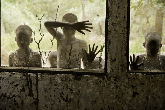 Steve McCurry, Omo Valley, Ethiopia, 08/08/2013. Children from Kara tribe looking through the windows. retouched_Kate Daigneault 08/26/2013