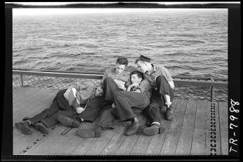 800px-Enlisted_men_reading_on_edge_of_elevator_aboard_USS_Lexington_CV-16._-_NARA_-_520895
