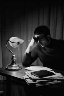 man working hard while writing
