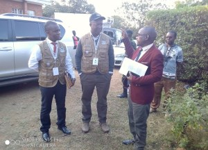Kachale listening attentively to Neno District Commissioner Blessings Nkhoma in red jacket