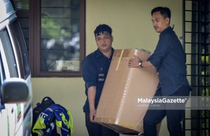 Beberapa anggota polis membawa keluar beberapa kotak dipercaya mengandungi barangan yang ada kaitan dengan siasatan kes membabitkan bekas Perdana Menteri, Datuk Seri Najib Tun Razak di Presint 10, Putrajaya. foto HAZROL ZAINAL, 11 JUN 2018.