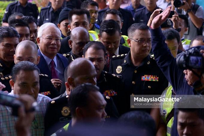 Bekas Perdana Menteri, Datuk Seri Najib Tun Razak sambil diiringi pegawai SPRM dan anggota polis ketika hadir untuk pertuduhan di Mahkamah Sesyen, Kompleks Mahkamah Kuala Lumpur. foto NOOR ASREKUZAIREY SALIM, 04 JULAI 2018
