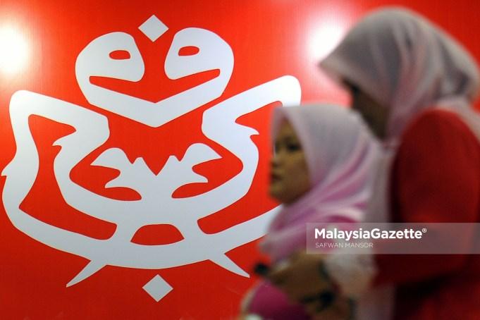 Dua perwakilan Pergerakan Puteri UMNO dilihat melintasi dinding yang dihiasi logo parti UMNO ketika tinjauan lensa Malaysia Gazette sempena Perhimpunan Agung UMNO 2017 di Pusat Dagangan Dunia Putra (PWTC), Kuala Lumpur. foto SAFWAN MANSOR, 07 DISEMBER 2017