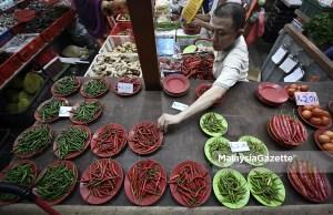 Seorang peniaga menyusun cili dan sayur-sayuran untuk dijual kepada pelanggan semasa tinjauan lensa MalaysiaGazette di Pasar Chow Kit, Kuala Lumpur. foto SYAFIQ AMBAK, 14 JUN 2018