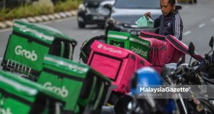 An e-hailing food delivery rider preparing to deliver food to the customer outside Sunway Putra Mall in Kuala Lumpur. PIX: MOHD ADZLAN / MalaysiaGazete / 15 APRIL 2021. commissions