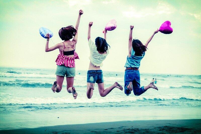 砂浜でジャンプしてはしゃぐ女性3人の後ろ姿